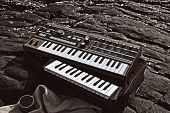 Music Synthesizer Lying On Rocks Close Up