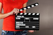 stock photo of premises  - Movie production clapper board in hands on grey background - JPG