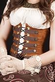 stock photo of corset  - A close up of a woman in her corset and gloves sitting proper - JPG