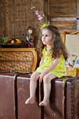Little barefooted girl in yellow dress sits on old big ragged suitcase