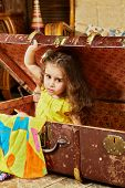 Little girl in yellow dress gets out from old big ragged fiber suitcase lying on floor in room