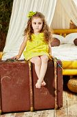 Little girl in yellow dress sits on old big ragged suitcase in room with big bed under tent