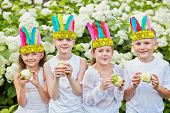 stock photo of indian apple  - Smiling children in white shirts and with stylized indian feather headdress on heads hold nibbled apples in their hands - JPG