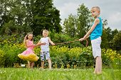 Children prepare to play tug-of-war, focus on boy in blue sleeveless shirt