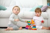 Two little kids sit on carpet and play with pyramids near sofa. Focus on left kid. Shallow depth of field.