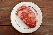 stock photo of ribeye steak  - Premium quality kobe beef ribeye steak in plate on wooden table - JPG