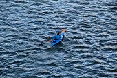 foto of canoe boat man  - Man in a blue canoe on a lake - JPG