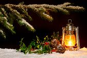 Christmas scene - an oil filled lantern burning bright with snow covered tree, holly and ivy lit up
