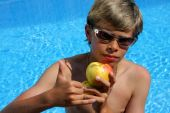 Boy With Sun Glasses And Apple At Swimming Pool