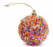 a christmas ball coated with nonpareils of different colors on a white background