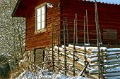 image of log fence  - Red log house with wooden fence in winter with snow in Sweden.