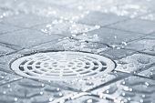 stock photo of floor covering  - Floor drain running water in shower tinted black and white image - JPG