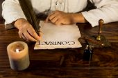 stock photo of inkpot  - a medieval man writes a contract with a feather - JPG