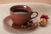 Coffee cup and saucer, cinnamon on a wooden table
