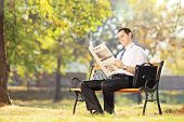 Young smiling man seated on a wooden bench reading a newspaper in a park