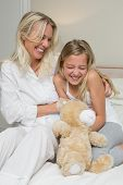 image of tickling  - Happy mother tickling daughter while sitting in bed at home - JPG