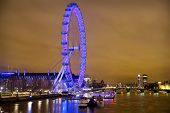 LONDON, UK - APRIL 5, 2014:  Night view of Big Ben, Houses of Parliament and London eye from the sou