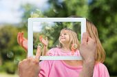 Hand holding tablet pc showing little girl playing with bubbles in the park
