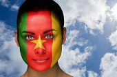Composite image of beautiful brunette in cameroon facepaint against bright blue sky with clouds