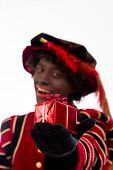 smiling zwarte piet ( black pete)  with gift . typical Dutch character part of a traditional event c