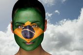 Composite image of beautiful brunette in brasil facepaint against bright blue sky with clouds