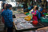 MAEKLONG, THAILAND - MARCH 24: Vendor sells fresh local fishery production on March 24, 2014 in famous Maeklong Railway Market also known as Talad Rom Hub or Umbrella Pulldown Market