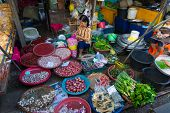 MAEKLONG, THAILAND - MARCH 24: Vendor sells fresh local agricultural production on March 24, 2014 in famous Maeklong Railway Market also known as Talad Rom Hub or Umbrella Pulldown Market