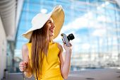 stock photo of panama hat  - Young traveling woman with photo camera and panama dressed in yellow dress standing in front of the airport or high - JPG