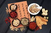 Chinese herbal medicine selection with mandarin calligraphy script describing the medicinal functions to maintain body and spirit health and balance body energy.