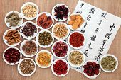 Chinese herbal medicine selection with calligraphy script describing the medicinal functions to maintain body and spirit health and balance body energy.