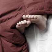 Person sleeping with feet poking out of red blankets on bed