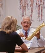 picture of chiropractic  - chiropractic doctor showing spine to a patient - JPG