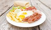 American  Breakfast With Fried Eggs, Bacon, Sausages, Toasts And Fresh Salad