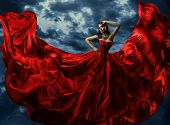 picture of flutter  - Woman in red evening dress waving gown with flying long fabric over artistic sky background - JPG