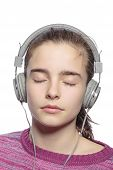 Female Teenager With Earphones And Closed Eyes Hears Music, Isolated On White