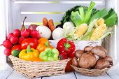 Vegetables in crate and in baskets on white wooden box background