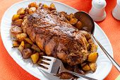 pic of frizzle  - a tasty roast with baked potatoes on a table with a tablecloth orange - JPG