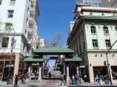 A Gateway Arch (dragon Gate) On Grant Avenue At Bush Street In Chinatown With People Walking Around