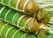 foto of bamboo leaves  - Banh tet for Lunar New Year Vietnam Tet food make from glutinous rice meat green bean cover by banana leaf tie by bamboo rope is traditional Vietnamese dishes - JPG