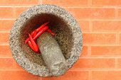 Red Chilies In A Mortar On An Orange Background.