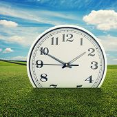 big white clock in the green grass over blue sky