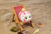 beach chair with euro currency on the sandy beach. symbol photo for costs in travel, vacation, holid