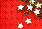 Cinnamon stars on red background with small dots and twig
