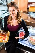 Female confectioner presenting tray of cake in bakery or pastry shop