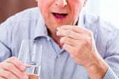 stock photo of overdose  - Old man taking overdoses medicaments at home - JPG