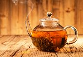 Teapot with blooming tea on wooden planks