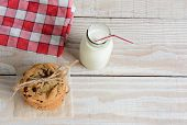 High angle shot of an after school snack of chocolate chip cookies and an old fashioned bottle of milk. The cookies are tied with twine and with a napkin on a rustic wood kitchen table.