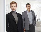 Portrait of business people standing at office, wearing suit, looking at camera, bright background. Attractive, confident caucasian woman.