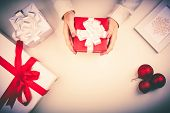 Red giftbox in female hands with other boxes, snowflake in frame and decorative toy balls near by