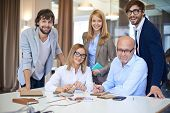 Company of successful business partners looking at camera in office